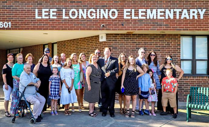 Honoree Lee Longino surrounded by his family at the school dedication ceremony on Tuesday, July 21.