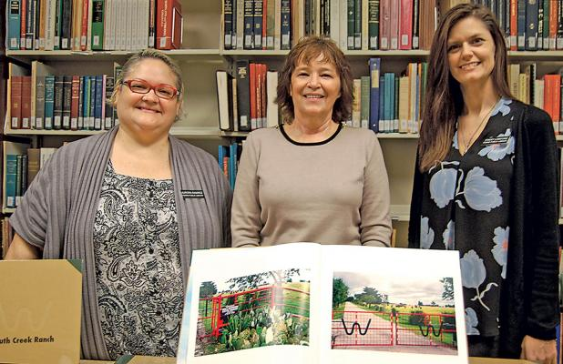 Shown displaying one the colorful  books depicting the beauty and history of South Creek Ranch in Ferris are Aurora Eamirez, Kathy Harrington, librarian and Stacy Lankford. Benefactor Bea Wallace donated the books for a library fundraiser. Wallace is the widow of Ray Wallace. Together they built 6,300-acre estate includin a four-story, 23,000 sq. foot mansion. The price of the books are yet to be determined. The library is located at 301 W. 10th St and can be reached by calling 972-544-3696.