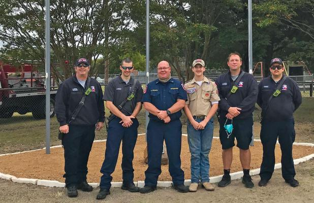 Following the flag ceremony, members of Ovilla's first responders pose in front of the new flagpoles. Pictured are K. Mooney, firefighter/paramedic; T. Burnett, firefighter; E. Homuth, battalion chief; Tyler Homuth, boy scout; P. Hobin, firefighter/paramedic; and J. Schepps, firefighter.