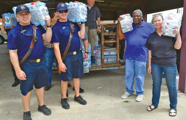 Following three days of no water on the east side of Interstate 45 in Ferris, Councilwoman Sherie Chapman (right) took action and obtained bottled water for the residents. Helping is Fire Captain Clayton Haughey, Firefighter Garrett Wright and Councilman Tommy Scott.