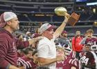 Head Coach Chris Ross hoists the Area Round Championship trophy over his Hawks football team at AT&T Stadium.